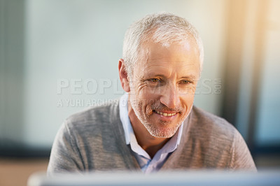 Buy stock photo Cropped shot of a mature businessman using his laptop in his office