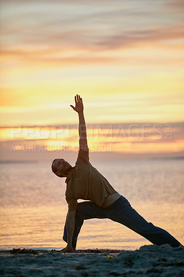 Buy stock photo Shot of a man practicing the triangle pose during his yoga routine at the beach