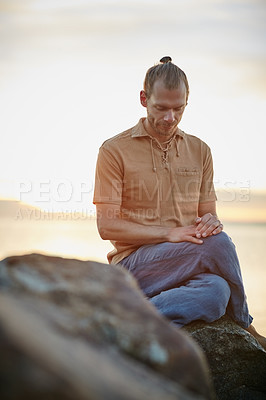 Buy stock photo Shot of a peaceful man sitting on a rock during his yoga routine at the beach
