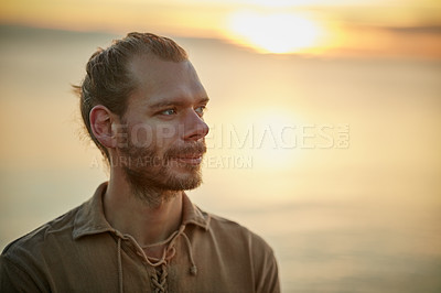 Buy stock photo Shot of a man relaxing at the beach during sunset