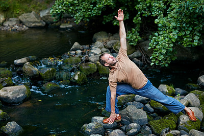 Buy stock photo Shot of a handsome man doing yoga stretches outdoors