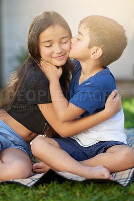 Buy stock photo Shot of a cute little boy giving his sister a kiss while they sit outside