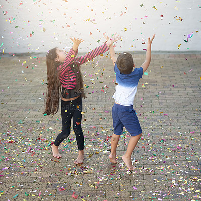 Buy stock photo Shot of a cute little boy and girl jumping to catch confetti as it falls outside their house