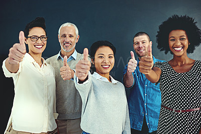 Buy stock photo Portrait of a diverse team of creative colleagues giving you a thumbs up in the studio