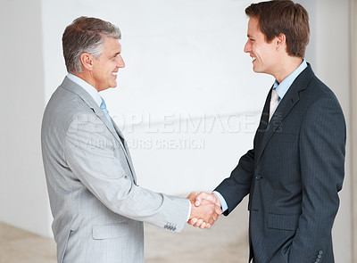 Buy stock photo Two business professionals shaking hands over a deal  in office