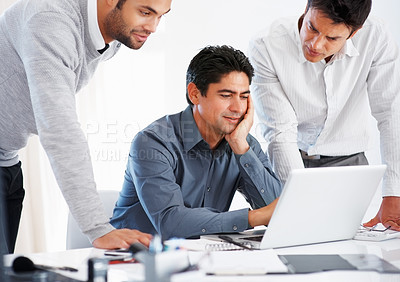 Buy stock photo Three male executives preparing business presentation on laptop