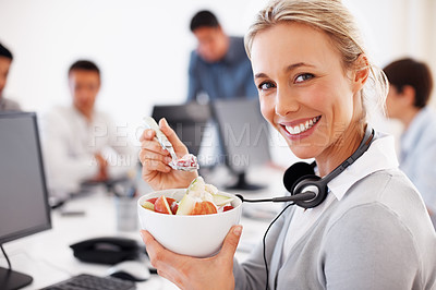 Buy stock photo Female call center employee eating at desk with colleagues in background