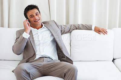 Buy stock photo Portrait of smart mature business man sitting on sofa and talking on mobile phone
