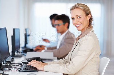 Buy stock photo Female customer service executive smiling with colleagues working in background