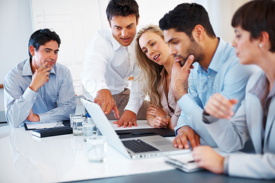 Buy stock photo Colleagues discussing project during business meeting with man pointing at laptop