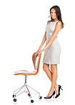 Pretty happy woman standing with a chair on white