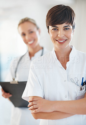 Buy stock photo Portrait of happy female doctor standing with hands folded and smiling with colleague in background