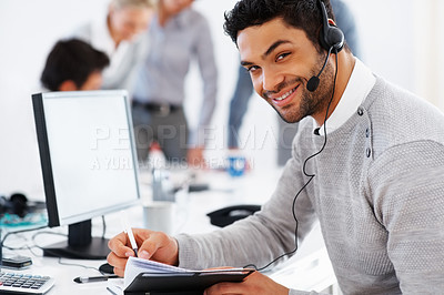 Buy stock photo Happy customer care executive noting something in diary with colleagues in background