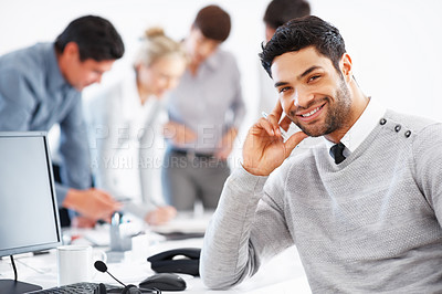 Buy stock photo Smiling business man sitting in chair with colleagues discussing in background