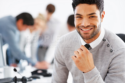 Buy stock photo Closeup of handsome male executive with colleagues discussing in background
