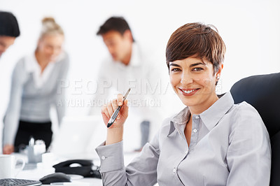 Buy stock photo Beautiful business woman holding pen with team discussing in background