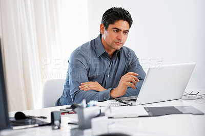 Buy stock photo Handsome business man sitting at his desk working on laptop