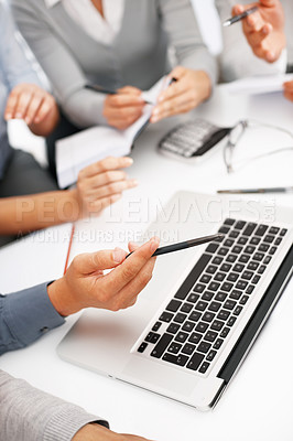 Buy stock photo Cropped image of business man pointing at laptop with colleagues in background