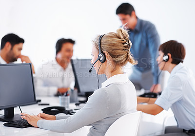 Buy stock photo Business woman wearing headset working on computer with colleagues in background