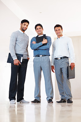 Buy stock photo Full length of three male partners standing in corridor and smiling