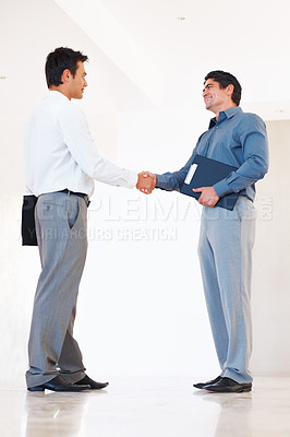 Buy stock photo Full length of male executives shaking hands in office corridor