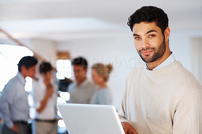 Buy stock photo Smart business man working on laptop with colleagues discussing in background