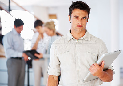 Buy stock photo Portrait of smart business man holding laptop and looking at you with colleagues discussing in background