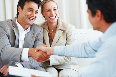 Buy stock photo Smiling couple with the man and financial advisor shaking hands during meeting