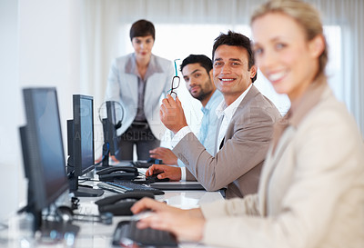 Buy stock photo Focus on smart male executive holding glasses and working with colleagues