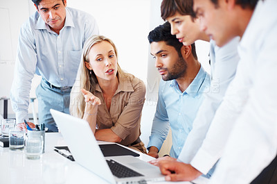 Buy stock photo Female executive sitting at table and discussing project with colleagues on laptop