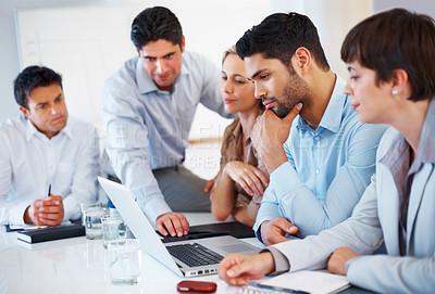 Buy stock photo Executives looking at laptop and studying project during meeting