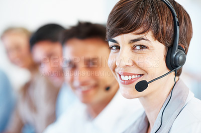 Buy stock photo Closeup of cute female executive wearing headphones and smiling with colleagues in background