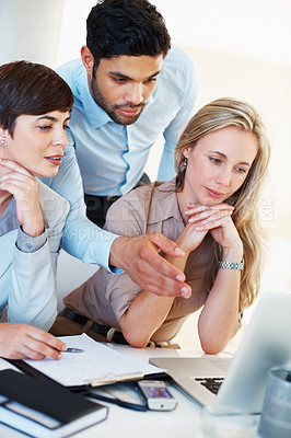 Buy stock photo Group of business people working with man pointing at laptop