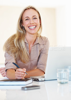 Buy stock photo Beautiful business woman at her desk taking notes from laptop