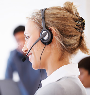 Buy stock photo Closeup of female customer care executive wearing headset with colleagues in background