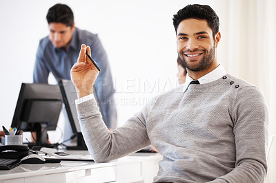 Buy stock photo Portrait of handsome business man holding pen with colleagues in background