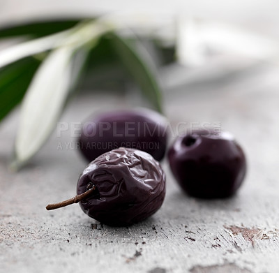 Buy stock photo Closeup of three dried black olives on floor