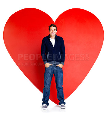 Buy stock photo Portrait of young man standing with hands in pocket against a big red heart on white background