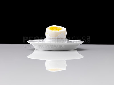 Buy stock photo Half cut boiled egg in a eggcup against black background