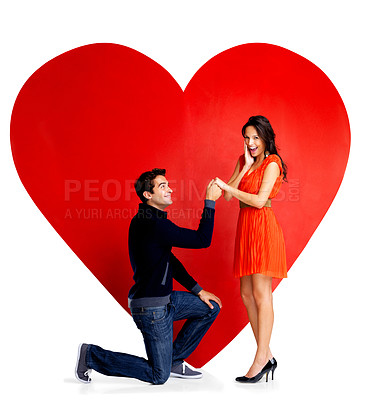 Buy stock photo Portrait of handsome young man proposing marriage to a beautiful woman against big red heart on white backgrounf