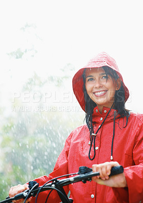 Buy stock photo Woman smiling on bike in pouring rain