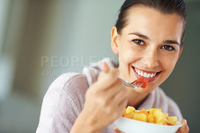 Buy stock photo Woman smiling while eating bowl of fruit