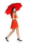 Beautiful young female walking with umbrella on white