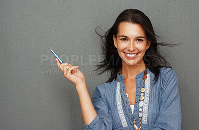 Buy stock photo Happy young woman smiling while holding a pen