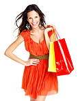 Smiling young woman holding shopping bags against white