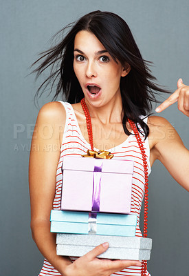 Buy stock photo Woman looking surprised as she points down to the stack of presents she's holding