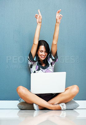 Buy stock photo Happy woman smiling while holding up her crossed fingers while looking at laptop