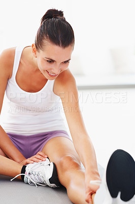 Buy stock photo Smiling young woman doing stretching on the floor