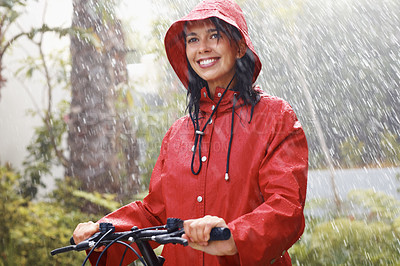 Buy stock photo Portrait of young woman in red raincoat on bike in rain