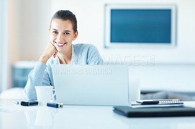 Buy stock photo Young woman smiling while using laptop